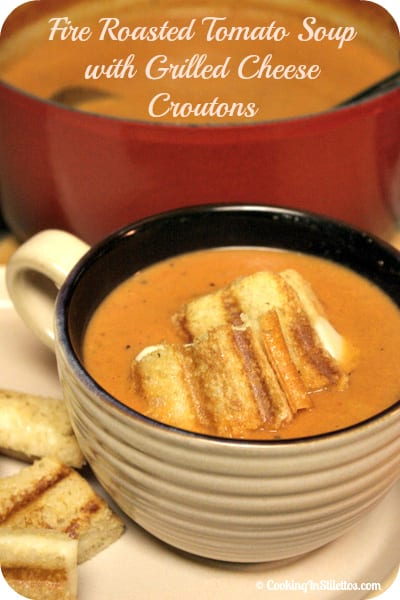 Fire Roasted Tomato Soup with Grilled Cheese Croutons is comfort in a cup and the recipe is foolproof. Smoky fire roasted tomatos are simmered with spices and a touch of cream and then topped with crispy grilled cheese croutons | Cooking In Stilettos