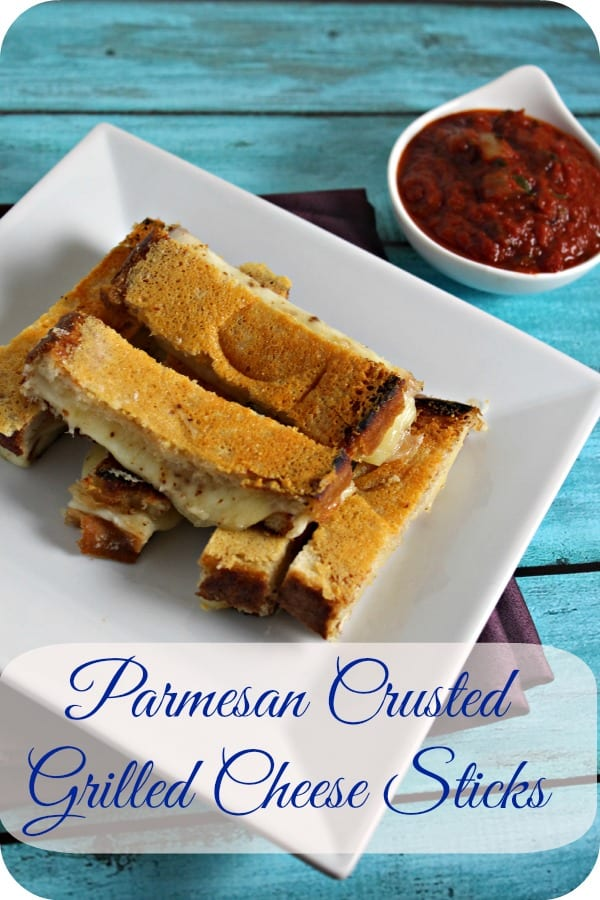 These Parmesan Crusted Grilled Cheese Sticks are a chic comforting bite on a old school classic. Gooey cheese layered with Aleppo pepper and a crunchy parmesan crust - what's not to love.  Serve with some easy homemade marinara sauce and you have a snack or a party bite that will be a hit | Cooking In Stilettos