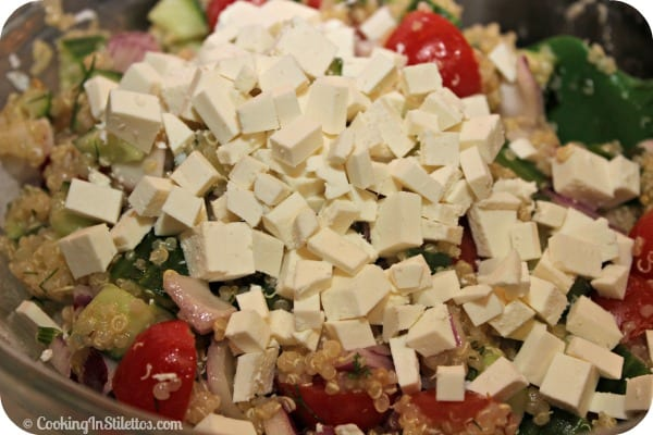 Cucumber Tomato Salad with Quinoa and Ricotta Salata - Adding the Cheese | CookingInStilettos.com