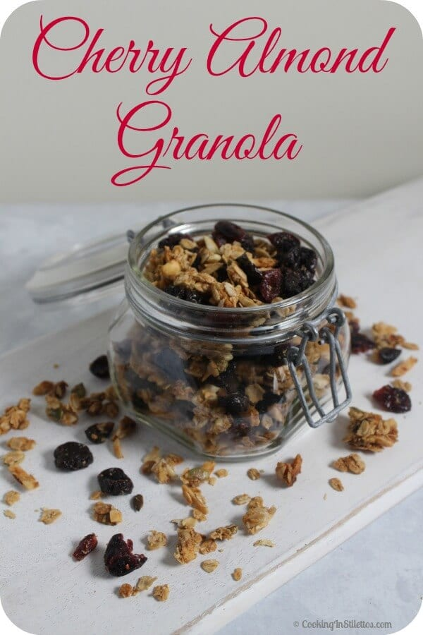 Cherry Almond Granola is a fabulous way to start your day! Dried cherries, cranberries and almonds are tossed with oats, spices and more for a fabulous sweet and crunchy bite. Perfect sprinkled on yogurt, mixed into muffins or even on its own, this Cherry Almond Granola will be a family favorite | Cooking In Stilettos