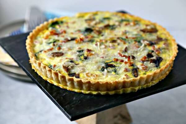 This Smoky Pancetta Quiche from CookingInStilettos.com is perfect for brunch, lunch or even dinner. Crisp pancetta, fresh arugula and buttery mushrooms are baked in a cheesy egg custard that will have your guests swooning with every bite. | Pancetta Quiche | Homemade Quiche | Breakfast for Dinner | Brunch Recipe | Quiche Recipe | Bacon Quiche | Breakfast | Brunch Quiche