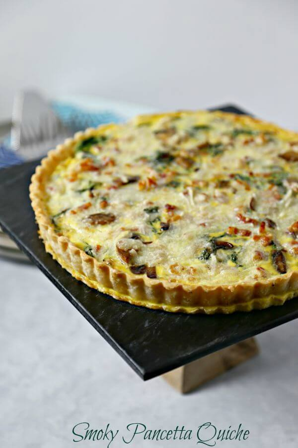 This Smoky Pancetta Quiche is perfect for brunch, lunch or even dinner. Crisp pancetta, fresh argula and buttery mushrooms are baked in a cheesy egg custard that will have your guests swooning with every bite. | Cooking In Stilettos