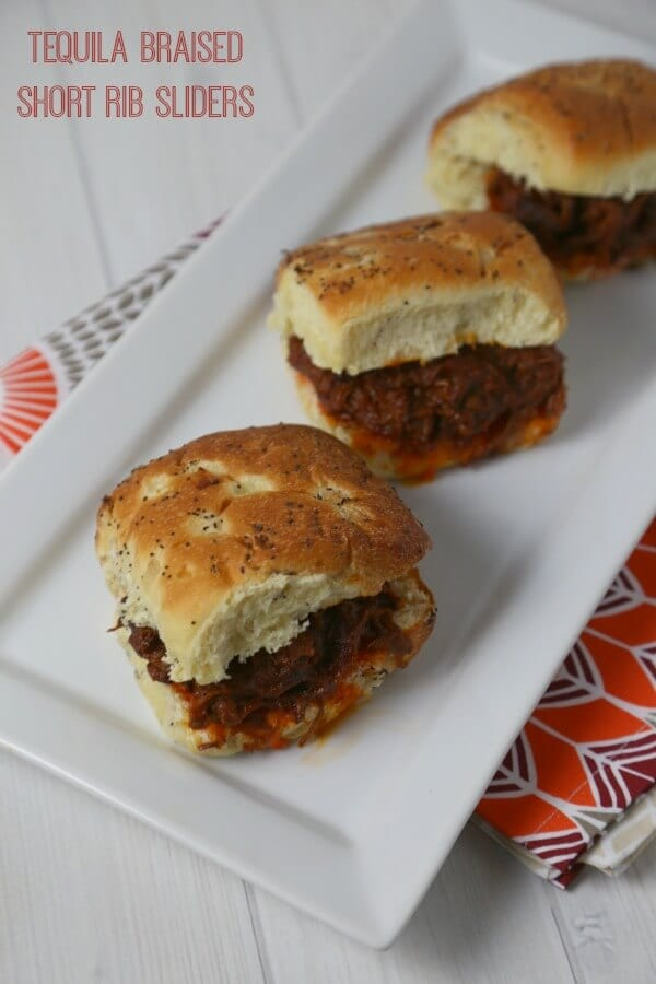 Tequila Braised Short Rib Sliders are the ultimate sliders. Rich beef short ribs are braised for hours in a chipotle tequila tomato sauce with a hint of spice and orange and then piled high on onion rolls. | Cooking In Stilettos