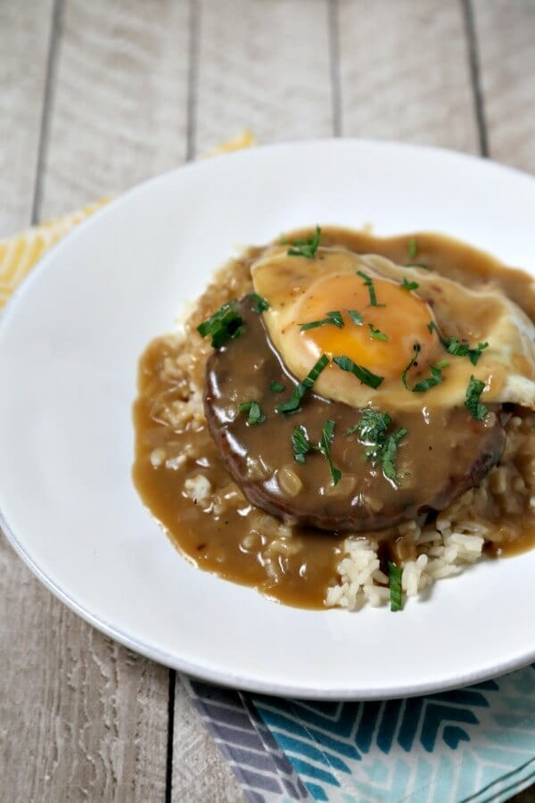 This Meatless Loco Moco with Savory Onion Gravy from CookingInStilettos.com is a delicious dinner idea. A spicy black bean veggie burger is nestled on a bed of rice, topped with a sunny side up egg and doused with savory onion gravy! Vegetarian | Meatless Monday | Veggie Burger Recipe | Healthy Hawaiian Recipe | Hawaiian | Comfort Food | Polynesian | Loco Moco