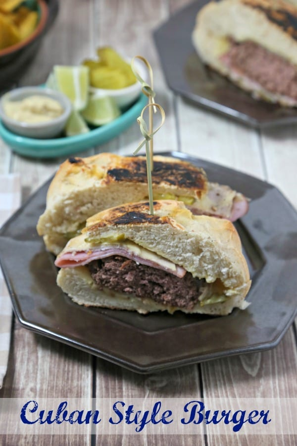 This Cuban Style Burger from CookingInStilettos.com brings all of the familiar flavors of a Cuban sandwich into an epic burger - perfect for your next cookout. Ham, roast pork and swiss are nestled on a pillowy bun with a juicy burger, crisp dill pickles and a mustardy spread | @CookInStilettos