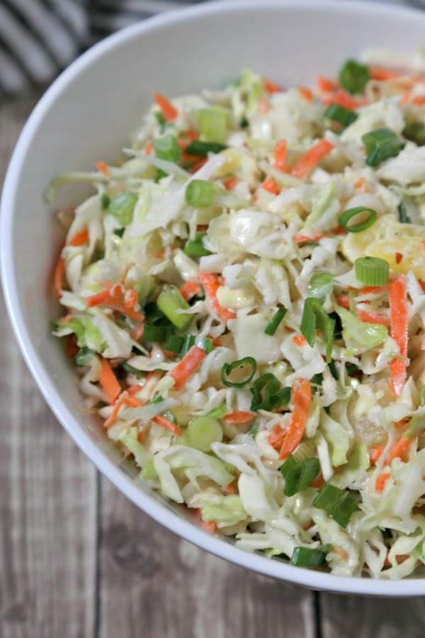 This easy Pineapple Slaw from CookingInStilettos.com will be a summertime favorite - sweet pineapple, spicy ginger & cabbage are tossed in a light yogurt dressing for the ultimate summer coleslaw | Cole Slaw | Pineapple | Healthy | BBQ | Cookout