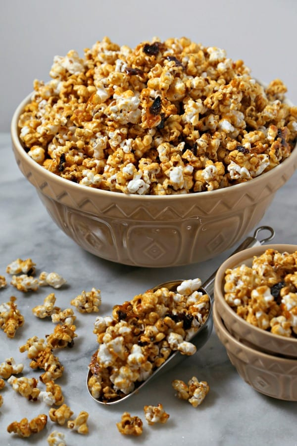 Bacon Bourbon Caramel Popcorn from CookingInStilettos.com is the ultimate salty sweet treat with a bit of a boozy kick. Crisp black pepper bacon is tossed with fluffy homemade popcorn in a buttery rich bourbon caramel and baked to perfection | Homemade | Caramel Popcorn | Boozy Bites | Bourbon Caramel | Bacon Caramel Popcorn | Caramel Popcorn Recipe