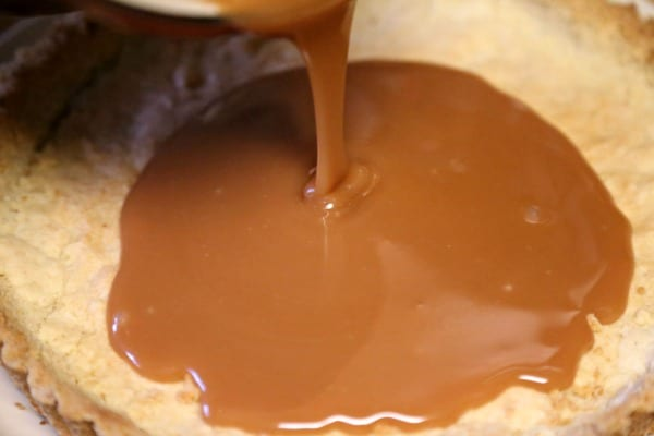 Gluten Free Chocolate Caramel Tart with Macadamia Nut Crust - Pouring the Caramel Layer | CookingInStilettos.com