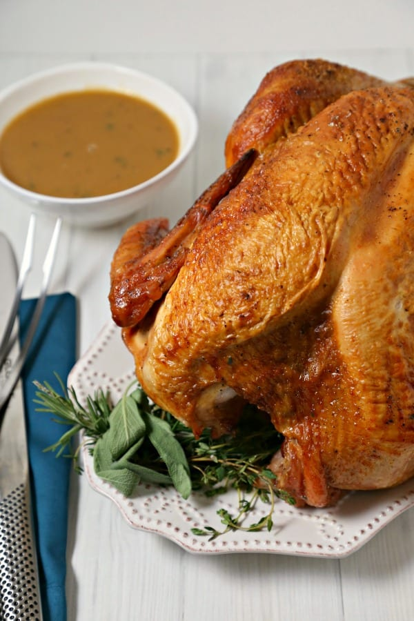 This Mustard Maple Glazed Roast Turkey with Homemade Gravy from CookingInStilettos.com is a flavorful twist on a classic roast turkey recipe. Golden roast turkey is glazed with a sweet and spicy mustard maple glaze that is packed with flavor and perfect for your holiday menu. #Turkey | #Gravy | Homemade | Roasted Turkey | #Holiday