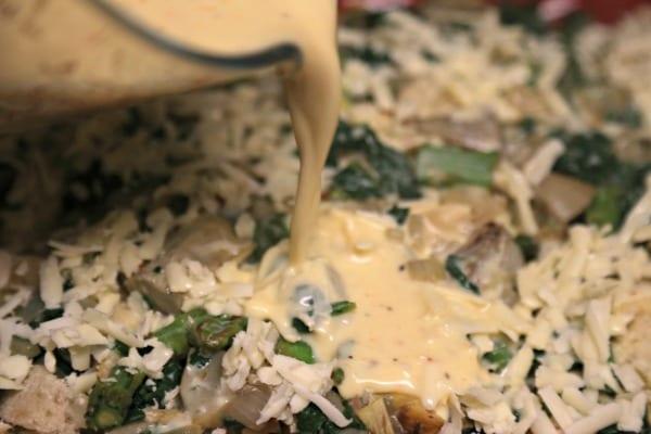 Spinach Artichoke and Asparagus Strata - Pouring the Custard   CookingInStilettos.com